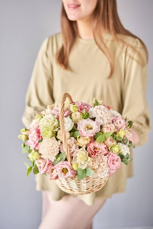Small flower shop and Flowers delivery. Flower arrangement in Wicker basket. Beautiful bouquet of mixed flowers in woman hand. Handsome fresh bouquet. Standard-Bild - 149889722