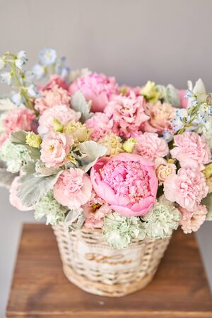 Beautiful flower composition a bouquet in a wicker basket. Floristry concept. Spring colors