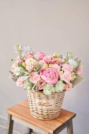 Beautiful flower composition a bouquet in a wicker basket. Floristry concept. Spring colors Standard-Bild - 149890448