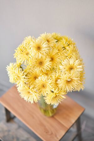 Beautiful flower composition. Sunny yellow gerbera flower heads in glass vase. Floristry concept. Spring colors