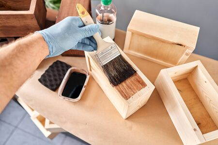 Man carpenter varnishing wooden crate for flowers with brush in her small business woodwork workshop. In your work, do you use stains or wood preservatives to show the wood pattern. Standard-Bild - 149889815