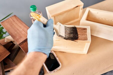 Man carpenter varnishing wooden crate for flowers with brush in her small business woodwork workshop. In your work, do you use stains or wood preservatives to show the wood pattern. Standard-Bild - 149889911