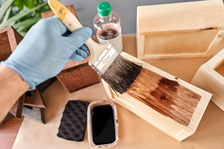 Man carpenter varnishing wooden crate for flowers with brush in her small business woodwork workshop. In your work, do you use stains or wood preservatives to show the wood pattern. Standard-Bild - 149889950