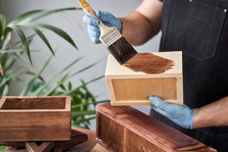 Man carpenter varnishing wooden crate for flowers with brush in her small business woodwork workshop. In your work, do you use stains or wood preservatives to show the wood pattern. Standard-Bild - 149889580