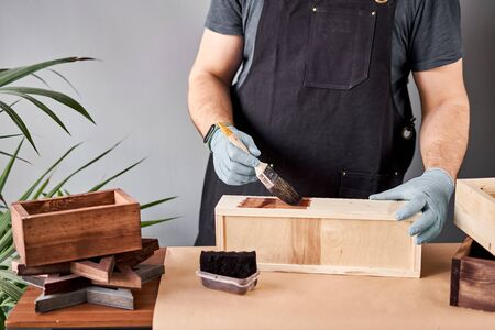 Man carpenter varnishing wooden crate for flowers with brush in her small business woodwork workshop. In your work, do you use stains or wood preservatives to show the wood pattern. Standard-Bild - 149890591