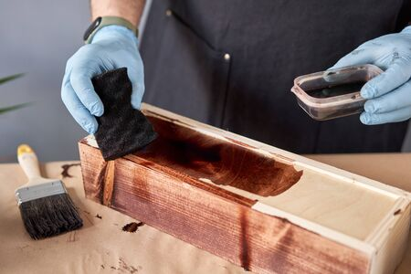 Man carpenter varnishing wooden crate for flowers with brush in her small business woodwork workshop. In your work, do you use stains or wood preservatives to show the wood pattern. Standard-Bild - 149890688