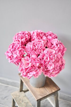 Beautiful pink hydrangea flowers in a vase on a table . Bouquet of light pink flower. Decoration of home. Wallpaper and background. fuchsia color Standard-Bild - 149890014