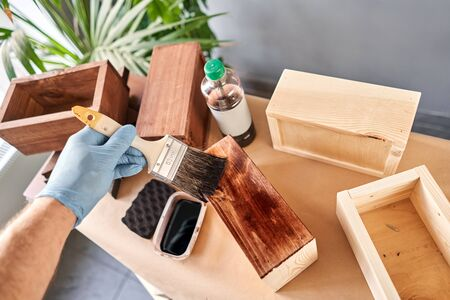 Man carpenter varnishing wooden crate for flowers with brush in her small business woodwork workshop. In your work, do you use stains or wood preservatives to show the wood pattern. Standard-Bild - 149890692