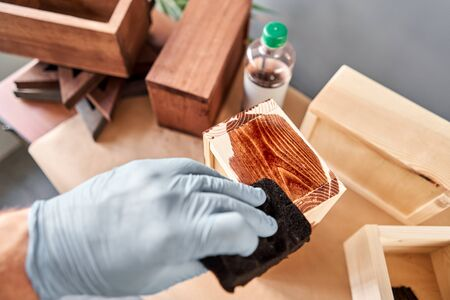 Man carpenter varnishing wooden crate for flowers with brush in her small business woodwork workshop. In your work, do you use stains or wood preservatives to show the wood pattern. Standard-Bild - 149890870