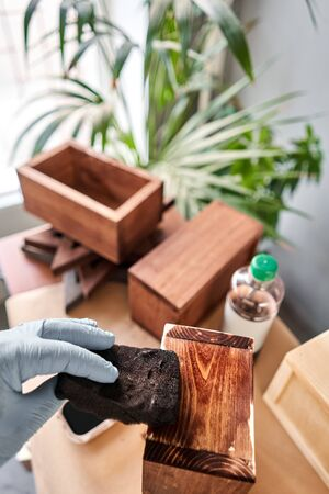 Man carpenter varnishing wooden crate for flowers with brush in her small business woodwork workshop. In your work, do you use stains or wood preservatives to show the wood pattern. Standard-Bild - 149890801