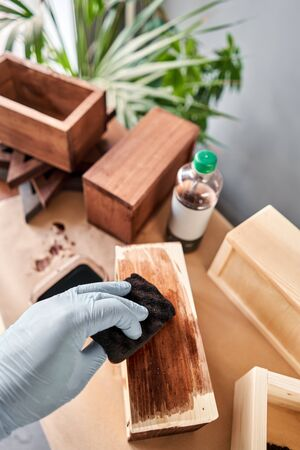 Man carpenter varnishing wooden crate for flowers with brush in her small business woodwork workshop. In your work, do you use stains or wood preservatives to show the wood pattern. Standard-Bild - 149894120