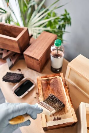 Man carpenter varnishing wooden crate for flowers with brush in her small business woodwork workshop. In your work, do you use stains or wood preservatives to show the wood pattern. Standard-Bild - 149894010
