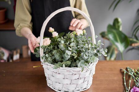 Floral shop concept . Florist woman creates flower arrangement in a wicker basket. Beautiful bouquet of mixed flowers. Handsome fresh bunch. Flowers delivery. Standard-Bild - 150162510