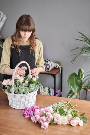 Small flower shop. Woman florist creating beautiful bouquet in a wicker basket. Work in flower shop. Flowers delivery.