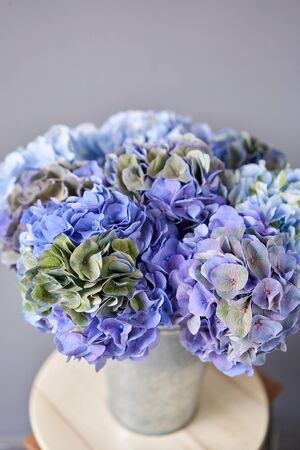 Beautiful blue hydrangea flowers in a vase on a table . Bouquet of light pink flower. Decoration of home. Wallpaper and background. Standard-Bild - 150162518