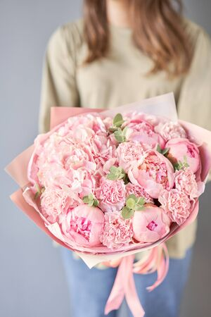 Bouquet of pink peonies and carnations in womans hands. Modern floral shop. Finished work of the florist. Delivery fresh cut flower from online store