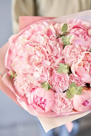Bouquet of pink peonies and carnations in womans hands. Modern floral shop. Finished work of the florist. Delivery fresh cut flower from online store Standard-Bild - 150162521