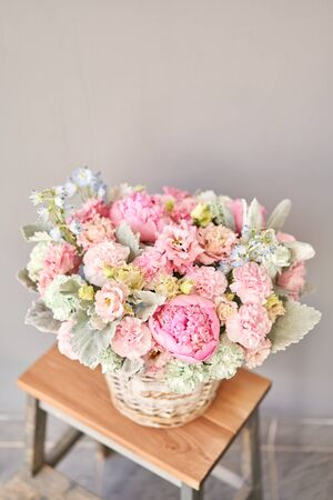 Beautiful flower composition a bouquet in a wicker basket. Floristry concept. Spring colors Standard-Bild - 150162531