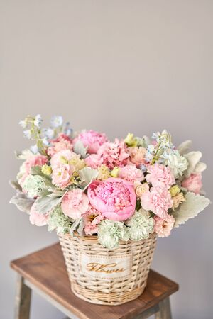 Beautiful flower composition a bouquet in a wicker basket. Floristry concept. Spring colors. Standard-Bild - 150162537