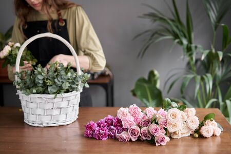 Floral shop concept . Florist woman creates flower arrangement in a wicker basket. Beautiful bouquet of mixed flowers. Handsome fresh bunch. Flowers delivery. Standard-Bild - 150166826