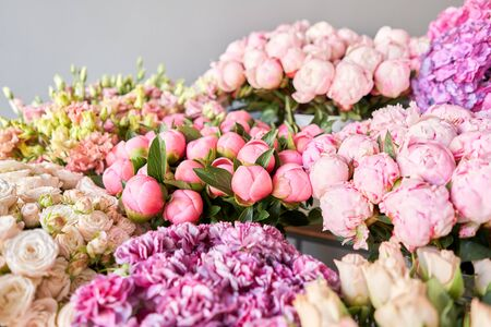 Many different colors on the stand or wooden table in the flower shop. Showcase. Background of mix of flowers. Beautiful flowers for catalog or online store. Floral shop and delivery concept. Top view. Copy space Standard-Bild - 150497035