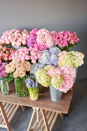 Many different colors on the stand or wooden table in the flower shop. Showcase. Background of mix of flowers. Beautiful flowers for catalog or online store. Floral shop and delivery concept. Top view. Copy space Standard-Bild - 150494890