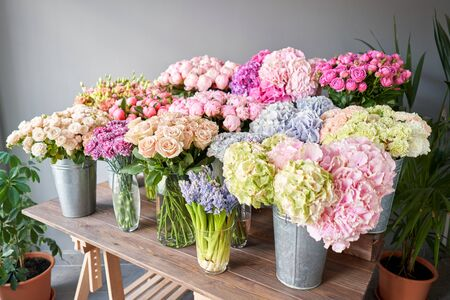 Many different colors on the stand or wooden table in the flower shop. Showcase. Background of mix of flowers. Beautiful flowers for catalog or online store. Floral shop and delivery concept. Top view. Copy space