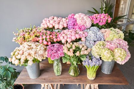 Many different colors on the stand or wooden table in the flower shop. Showcase. Background of mix of flowers. Beautiful flowers for catalog or online store. Floral shop and delivery concept. Top view. Copy space Standard-Bild - 150497038