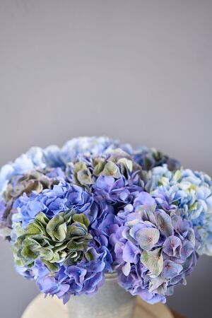 Beautiful blue hydrangea flowers in a vase on a table . Bouquet of light pink flower. Decoration of home. Wallpaper and background. Standard-Bild - 150495679
