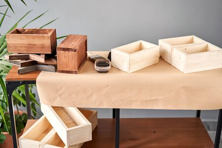 A set of blanks of wooden boxes for flower compositions. Small business woodwork workshop. In your work, do you use stains or wood preservatives to show the wood pattern. Standard-Bild - 150495535