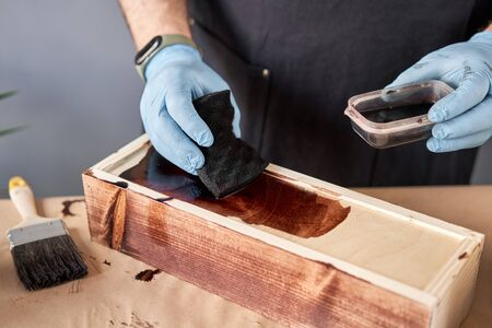 Man carpenter varnishing wooden crate for flowers with brush in her small business woodwork workshop. In your work, do you use stains or wood preservatives to show the wood pattern. Standard-Bild - 150495566
