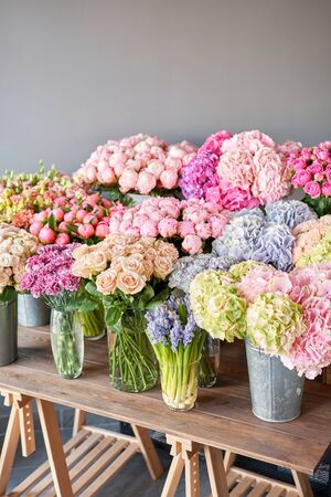 Many different colors on the stand or wooden table in the flower shop. Showcase. Background of mix of flowers. Beautiful flowers for catalog or online store. Floral shop and delivery concept. Top view. Copy space Standard-Bild - 150497053