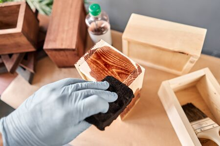 Man carpenter varnishing wooden crate for flowers with brush in her small business woodwork workshop. In your work, do you use stains or wood preservatives to show the wood pattern. Standard-Bild - 150496540