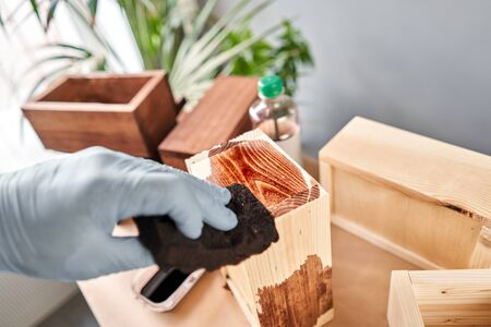 Man carpenter varnishing wooden crate for flowers with brush in her small business woodwork workshop. In your work, do you use stains or wood preservatives to show the wood pattern. Standard-Bild - 150496517