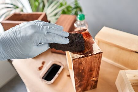 Man carpenter varnishing wooden crate for flowers with brush in her small business woodwork workshop. In your work, do you use stains or wood preservatives to show the wood pattern. Standard-Bild - 150496574