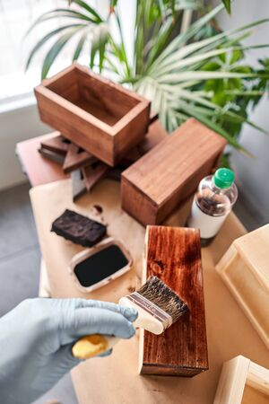 Man carpenter varnishing wooden crate for flowers with brush in her small business woodwork workshop. In your work, do you use stains or wood preservatives to show the wood pattern. Standard-Bild - 150497068