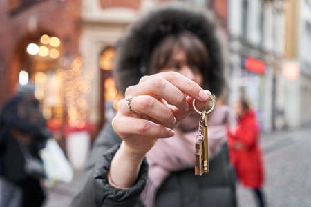 Mortgage or rent concept. Womans holding key with wooden house keychain . Real estate, hypothec, moving home or renting property. Christmas mood in blurred background.