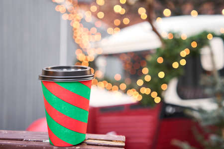 closeup cup of mulled wine with blurred background of winter wonderland, a Christmas Market in European small city