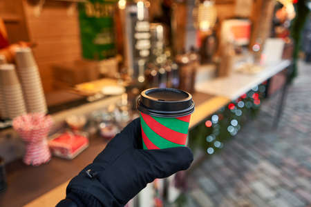 Christmas Market in European small city. Hand holding a cup of mulled wine with blurred background of winter wonderland.