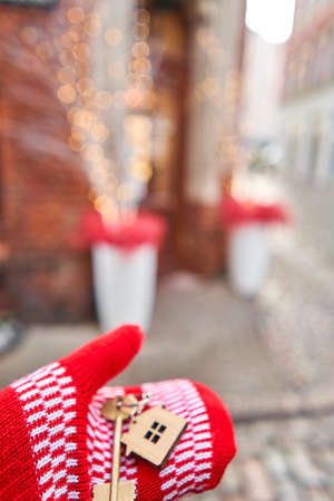 Christmas mood in blurred background. Hand in red mitten holding key with house shaped keychain. Mortgage or rent concept.