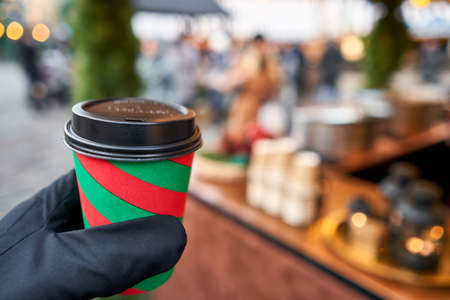 Christmas Market in European small city. Hand holding a cup of mulled wine with blurred background of winter wonderland, a