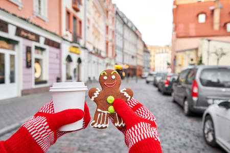 Hand in red mitten holding coffee cup and a smiling gingerbread man. Christmas mood in blurred background. Christmas market in old town European small city.