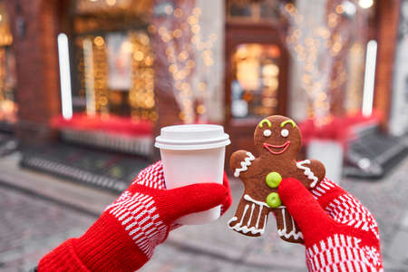 Christmas market in old town European small city. Hand in red mitten holding coffee cup and a smiling gingerbread man. Christmas mood in blurred background.