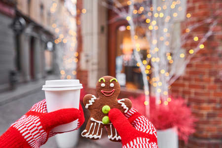 Smiling gingerbread man and christmas mood in blurred background. Christmas market in old town European small city. Standard-Bild