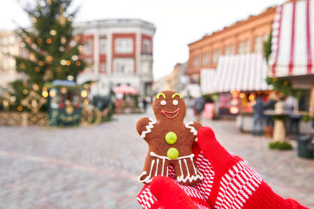Christmas market in old town European small city. Hand in red mitten holding a smiling gingerbread man and christmas mood in blurred background.