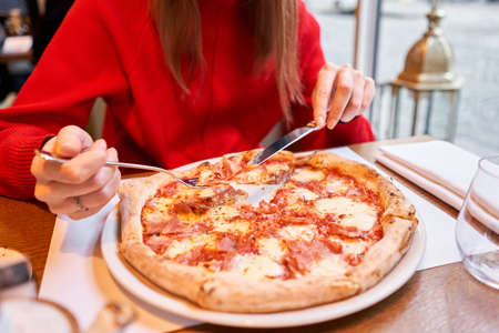 Woman eats with knife and fork a pizza capricciosa. Pizza with mozzarella tomatoes, Artichoke, black olives and basil. Neapolitan pizza from wood-burning stove. lunch in an Italian restaurant. Stock Photo