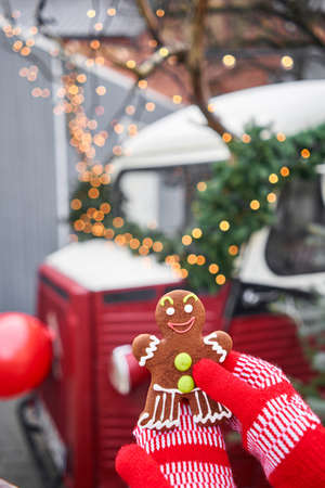 Hand in red mitten holding a smiling gingerbread man and christmas mood in blurred background. Christmas market in old town European small city.