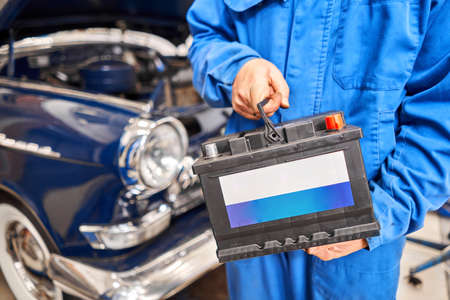 Engine engineer is replacing car battery because car battery is depleted. concept car maintenance. Against the background of a retro car of the 50s Standard-Bild
