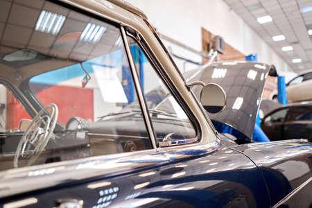 Garage with retro cars. Mechanic in classic car restoration workshop