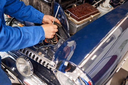 Retro car, Amateur collector repairs his car. Mechanic hands checking up of serviceability of the car in open hood, close up. repairs electrical wiring.